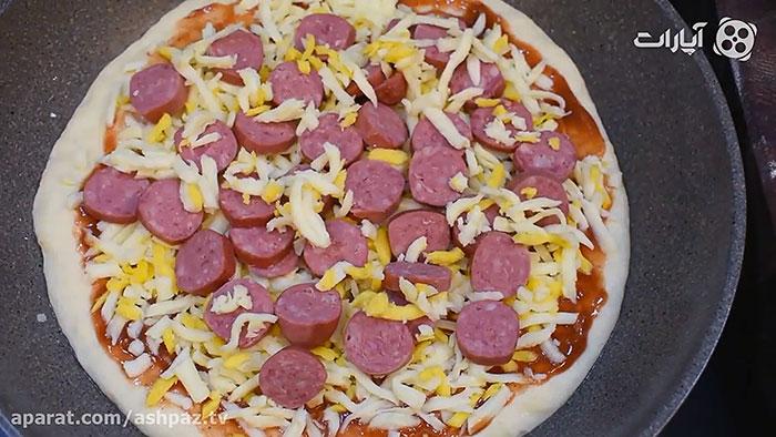 چیدن پپرونی برش خورده روی پیتزا